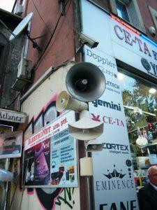 Imagen urbana tomada en Istanbul. Se ven altavoces en la calle y una cámara para grabar.