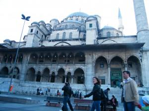 las cúpulas de la mezquita, su fachada preciosa y las personas paseando en frente de ella.